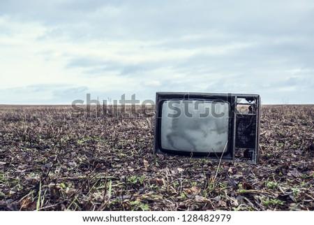 old broken TV is an autumn field
