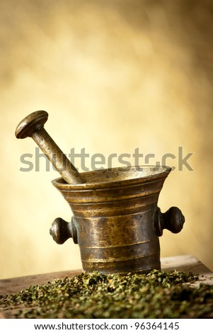 Old bronze mortar and pestle with dry spice herbs on yellow background