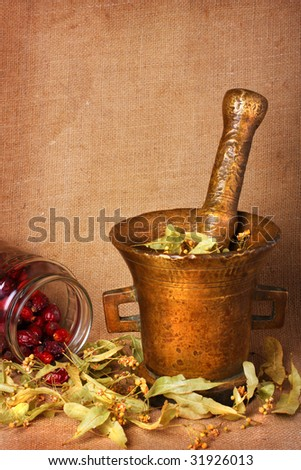 Old bronze mortar with dry herbs and rose hips on sacking background