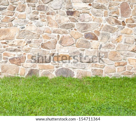 Old brown and gray cobblestone wall with grass in the foreground