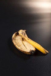 Old brown banana peel close up, on black background.