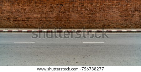 Old brown brick wall with concrete sidewalk and asphalt road with red and white traffic sign