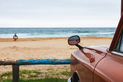 Old brown car on the sandy beach with a blue log fence, summer vacation at the sea.
