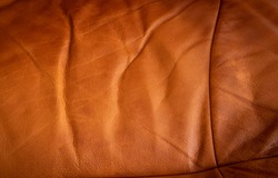Old brown leather texture background. Aged orange sofa skin pattern, grunge dark cover surface top view with natural day light