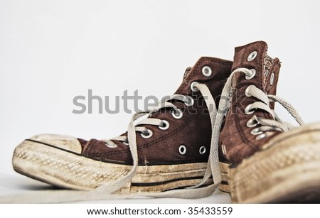 Old brown sneakers with white laces.