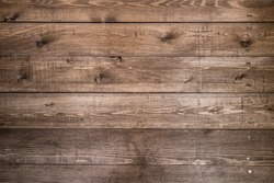 Old brown wood background made of dark natural wood in grunge style. The view from the top. Natural raw planed texture of coniferous pine. The surface of the table to shoot flat lay. Copy space
