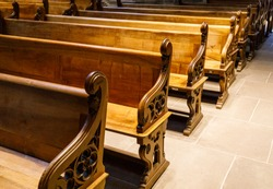 Old brown wooden benches in a church or cathedral