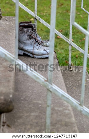 Old brown work boots. Boots smeared with white paint. Dirty boots on the stairs. Dirty old workboots on stairs.