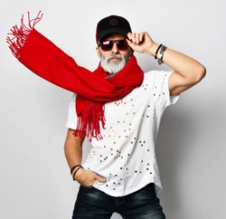 Old brutal senior rich man in white designer t-shirt cap and long red scarf stylish fashionable men isolated on white background
