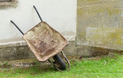 Old builders wheelbarrow resting against wall and standing on grass