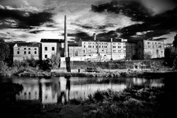 Old building and a factory in black and white. In Latvia city of Bauska, next to river Lielupe, all abandoned with dramatic sky and look