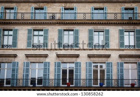 Old building exterior in Paris, France with windows and balconies