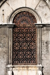 Old building in Venice, Italy. Vintage window with rusty decorative bars.
