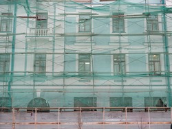 Old building is covered with a net. Concept of repair, restoration of buildings.
