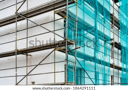 Old building under construction with scaffolds. Construction site. Scaffolding on multi storey building facade during renovation. Photo stock ©