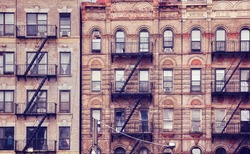 Old buildings with fire escapes, one of the New York City symbols, color toned picture, USA.