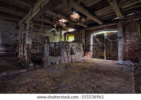 Old, built of wood and brick, abandoned barn.