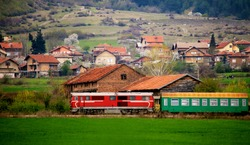 old bulgarian train passing through spring green meadows neat small village