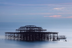 Old burned Western Brighton Pier remains sitting at sea waters at twilight sunset light with blue cloudy sky behind