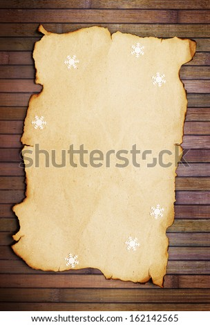 Old burnt empty paper  and decorative snowflakes,vertical