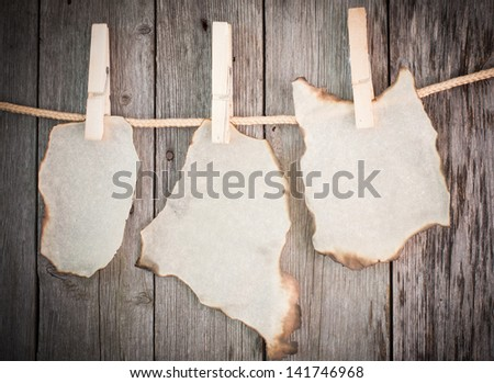 old burnt paper attach to rope with clothes pins on wooden background