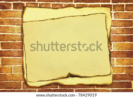 old burnt paper with burnt edges over grunge brick wall background
