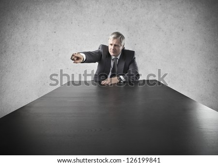 Old businessman at the head of a long black table indicates someone with aggression