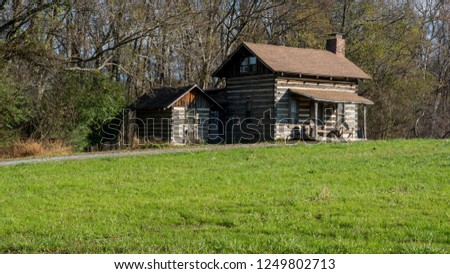Old cabin in field next to woods with shed/outhouse next to it