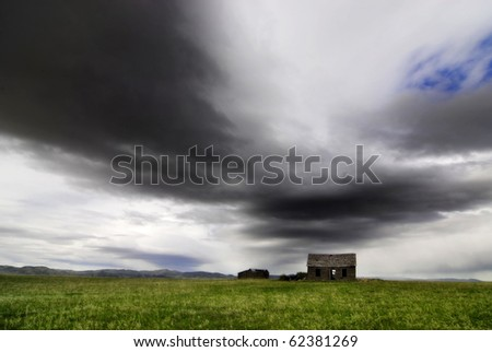 Old cabin in field with storm clouds in sky