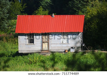 old cabin with red roof in...