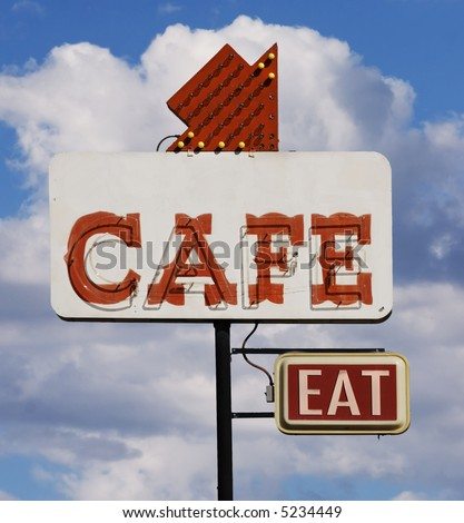 "Old cafe sign with the word ""eat"" against a cloudy sky."