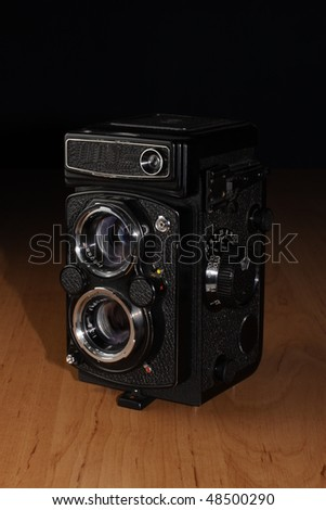 Old camera for middle format film on wooden table