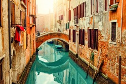 Old canal with boats and bridge in Venice, Italy. Street with old Italian architecture of Venice. Cityscape of Venice at sunset.