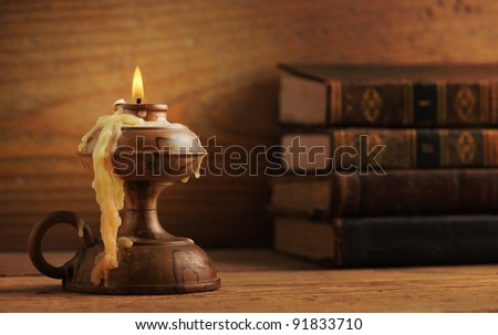 old candle on a wooden table, old books in the background, similar photo in my portfolio