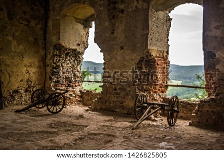Old cannons in the ruin of a castle pointing from the windows #1426825805