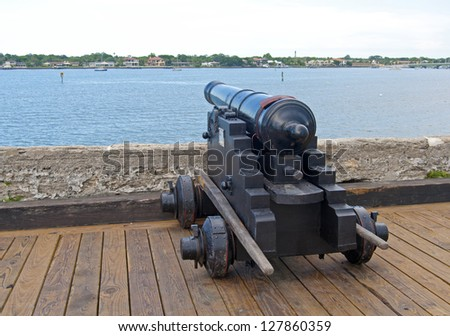 Old canon aiming at the sea, on an overcast day. Old Castillo de San Marcos, St. Augustine, Florida
