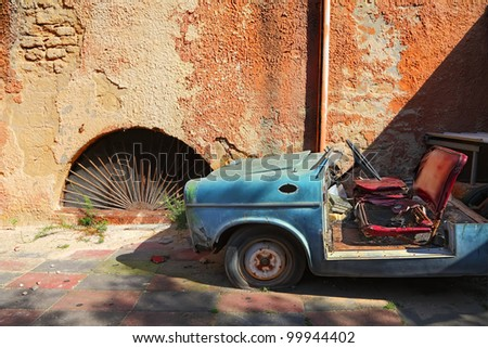 Old car on the grunge wall background