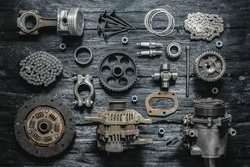 Old car spare parts on a black wooden workbench flat lay background.