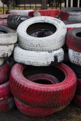 Old car tires are painted white and red. Old tires as a protective fence. Household waste. Environmental disaster. Trash. Old tires. Tires on the ground.