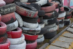Old car tires are painted white and red. Old tires as a protective fence. Household waste. Environmental disaster. Garbage. Old tires. Tires on the ground.