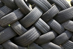 Old car tires in row as a fence  in a rural courtyard. Old tires functions as a protective fence. Household waste. Environmental disaster.  Old tires as garbage on the ground