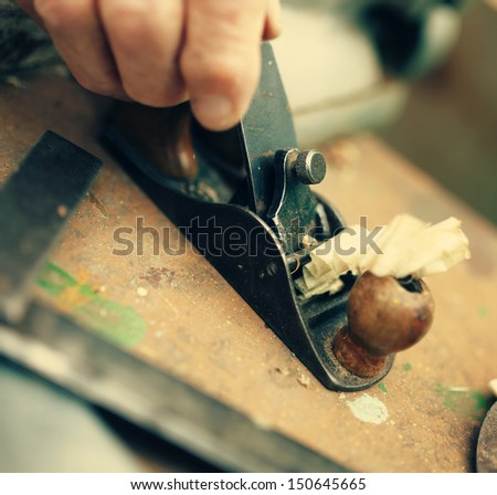 Old carpenter working with wood