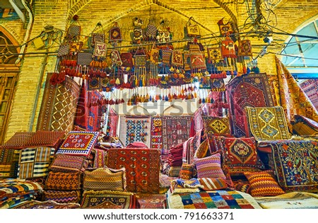 Old carpet stall with kil for each taste - knotted-pile Persian carpets, woven nomadic tribal rugs, handmade or machine made, woolen or cotton, everything can be found in Vakil Bazaar, Shiraz, Iran. #791663371