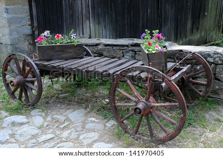 Old cart and flowers in the wooden flower boxes in Bulgaria