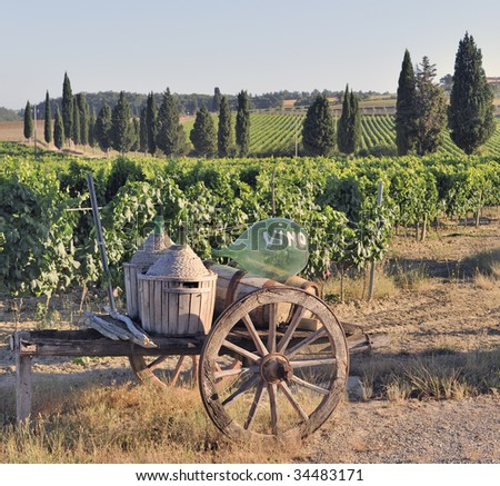 Old cart and wine flasks in front of vineyard in Tuscany, Italy