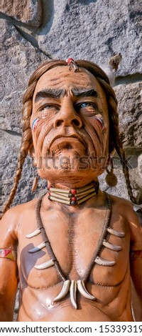 Old carved cigar store Indian - stone wall as background