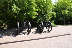 Old cast iron cannons. Cannons on wheels in the city park. Summer landscape of the park.