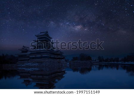 Old castle in japan. Matsumoto castle against night sky. Castle in Winter with milky way on sky .Travel Matsumoto Castle with frozen pond in Winter. A Japanese premier historic castles