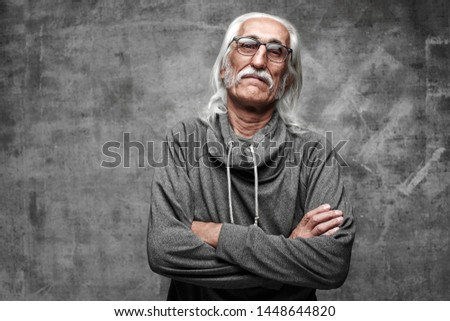 Old Caucasian gray-haired cool grandfather with glasses incredulously looks into the camera with crossed arms and serious face with copy space in studio