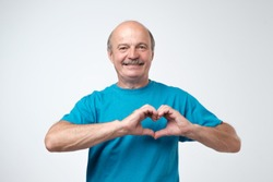 old caucasian man in blue t-shirt making out of hands heart. Doing charity work, take care of the health, or being in love